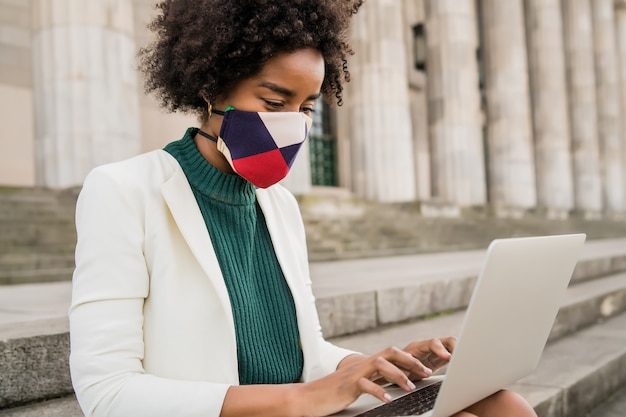 Afro zakenvrouw beschermend masker dragen en met behulp van haar laptop zittend op de trap buiten