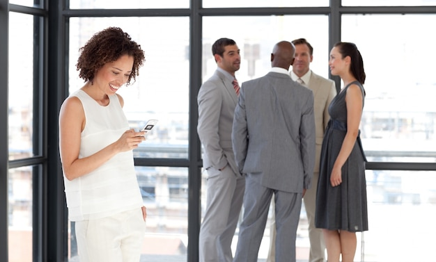 Afro zakenvrouw die een telefoon op het werk met zijn collega's