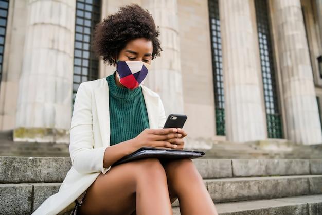 Afro zakenvrouw dragen beschermend masker en met behulp van haar mobiele telefoon zittend op de trap buiten op straat. bedrijfs- en stedelijk concept.