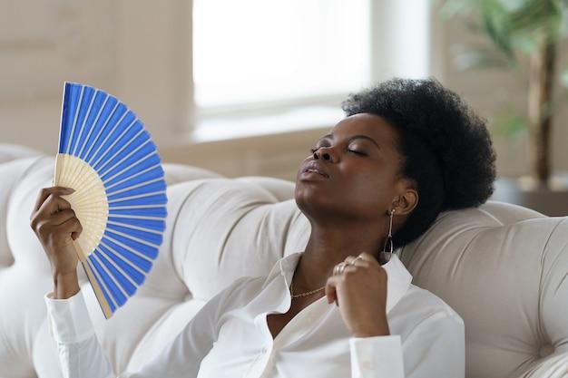 Afro zakenvrouw lijdt aan hitteberoerte zittend in de huiskamer met behulp van zwaaiende ventilator