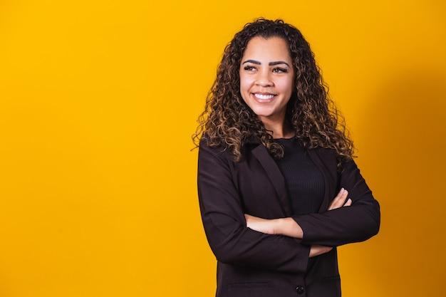 Afro zakenvrouw. zelfverzekerde zwarte vrouw in pak poseren met gevouwen armen op gele achtergrond, horizontale banner, brede afstandsschot, panorama