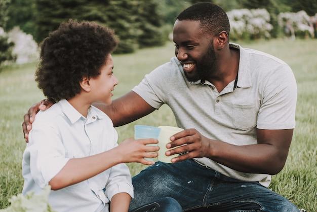 Afro zoon en vader juichen juice op picnic.