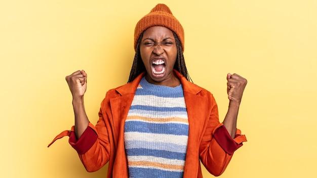 Afro zwarte mooie vrouw die agressief schreeuwt met een boze uitdrukking of met gebalde vuisten om succes te vieren