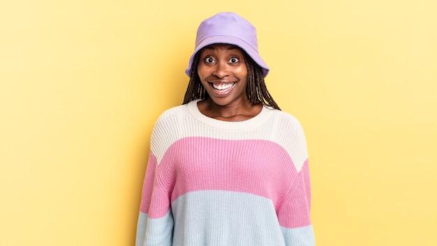 Afro zwarte mooie vrouw die er blij en aangenaam verrast uitziet, opgewonden met een gefascineerde en geschokte uitdrukking