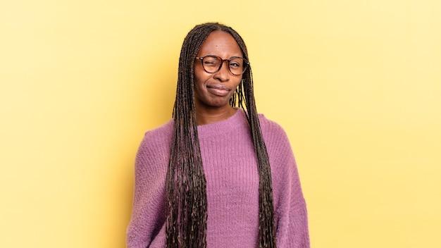 Afro-zwarte mooie vrouw die er gelukkig en vriendelijk uitziet, lacht en je met een positieve houding aankijkt