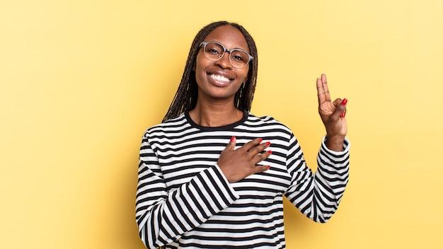 Afro zwarte mooie vrouw die er gelukkig, zelfverzekerd en betrouwbaar uitziet, glimlacht en een overwinningsteken toont, met een positieve houding