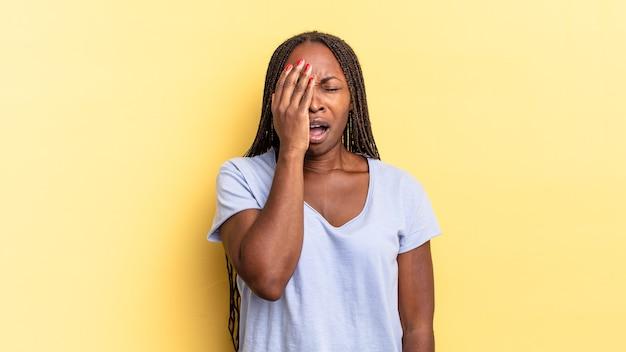 Afro-zwarte mooie vrouw die er slaperig, verveeld en geeuwend uitziet, met hoofdpijn en een hand die de helft van het gezicht bedekt