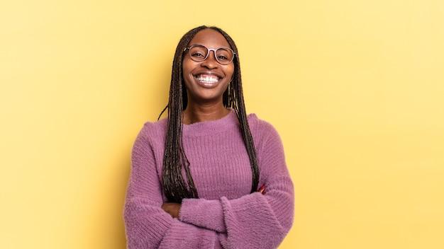 Afro-zwarte mooie vrouw die eruitziet als een gelukkige, trotse en tevreden presteerder die lacht met gekruiste armen