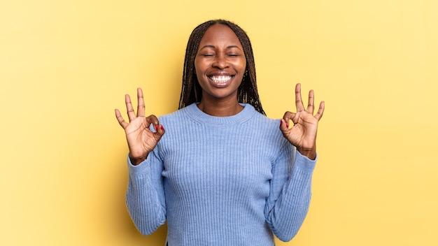 Afro-zwarte mooie vrouw die geconcentreerd en mediterend kijkt, tevreden en ontspannen voelt, denkt of een keuze maakt