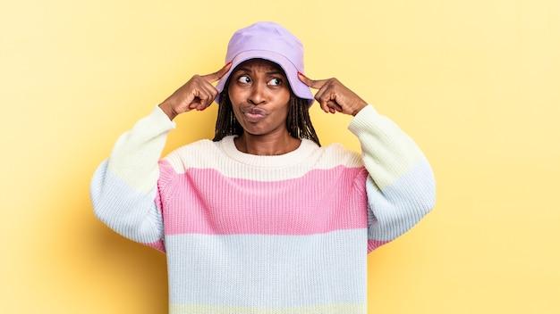Afro-zwarte mooie vrouw die geconcentreerd kijkt en hard nadenkt over een idee, zich een oplossing voor een uitdaging of probleem voorstelt