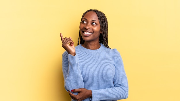 Afro-zwarte mooie vrouw die gelukkig glimlacht en zijwaarts kijkt, zich afvraagt, denkt of een idee heeft