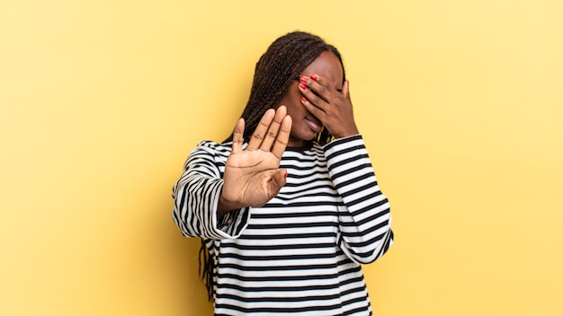 Afro-zwarte mooie vrouw die het gezicht bedekt met de hand en de andere hand naar voren steekt om de camera te stoppen, foto's of afbeeldingen te weigeren