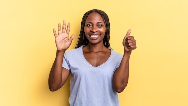Afro-zwarte mooie vrouw die lacht en er vriendelijk uitziet, nummer zes of zesde toont met de hand naar voren, aftellend