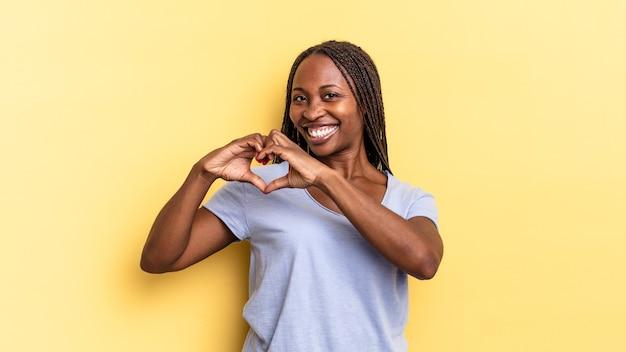 Afro-zwarte mooie vrouw die lacht en zich gelukkig, schattig, romantisch en verliefd voelt, hartvorm maakt met beide handen