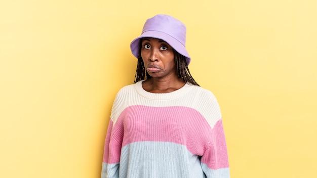 Afro-zwarte mooie vrouw die verdrietig en zeurt met een ongelukkige blik, huilt met een negatieve en gefrustreerde houding