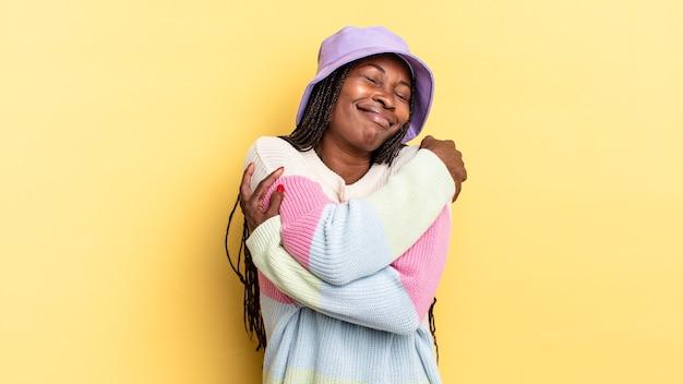 Afro-zwarte mooie vrouw die verliefd is, glimlacht, knuffelt en zichzelf knuffelt, vrijgezel blijft, egoïstisch en egocentrisch is