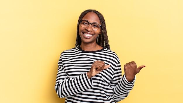 Afro-zwarte mooie vrouw die vrolijk en nonchalant lacht en wijst naar de ruimte aan de zijkant, voelt zich gelukkig en tevreden