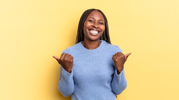 Afro-zwarte mooie vrouw die vrolijk lacht en er gelukkig uitziet, zich zorgeloos en positief voelt met beide duimen omhoog