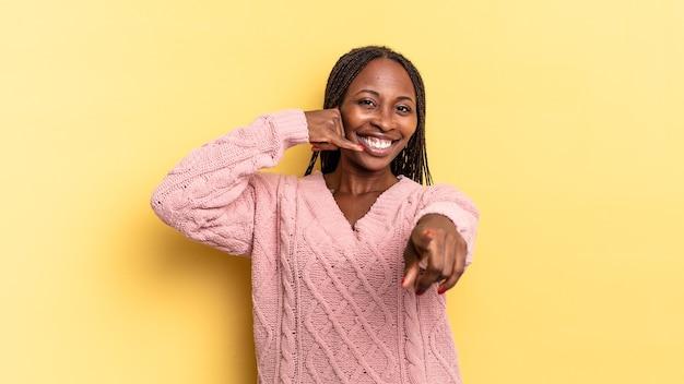 Afro zwarte mooie vrouw die vrolijk lacht en naar de camera wijst terwijl ze je later belt, gebaar, pratend aan de telefoon