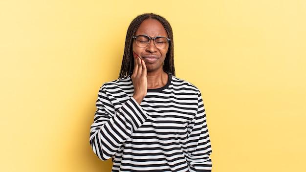 Afro-zwarte mooie vrouw die wang vasthoudt en pijnlijke kiespijn heeft, zich ziek, ellendig en ongelukkig voelt, op zoek naar een tandarts