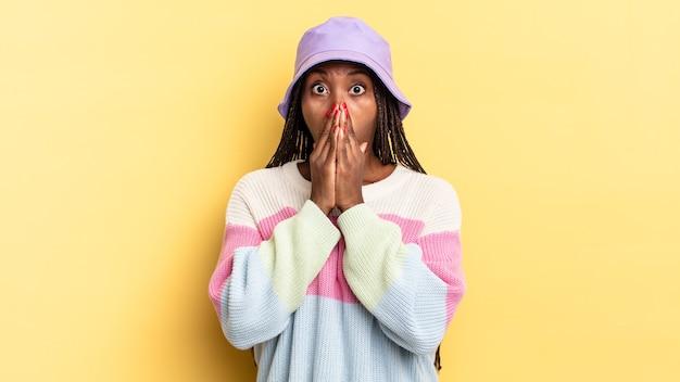 Afro-zwarte mooie vrouw die zich bezorgd, overstuur en bang voelt, de mond bedekt met handen, er angstig uitziet en het verprutst heeft