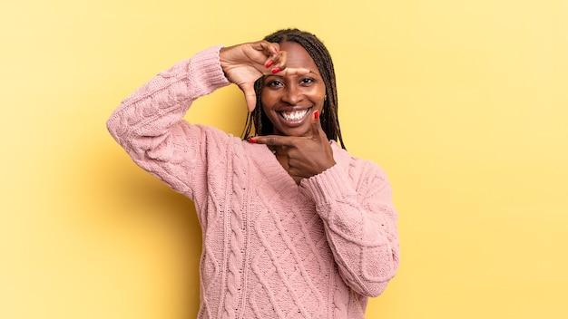 Afro zwarte mooie vrouw die zich gelukkig, vriendelijk en positief voelt, lacht en een portret of fotolijst maakt met handen