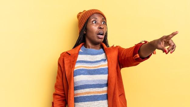 Afro-zwarte mooie vrouw die zich geschokt en verrast voelt, wijst en vol ontzag naar boven kijkt met een verbaasde blik met open mond