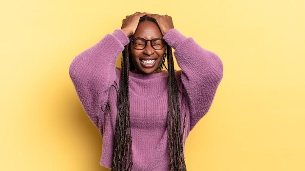 Afro zwarte mooie vrouw die zich gestrest en angstig, depressief en gefrustreerd voelt met hoofdpijn, beide handen opstekend