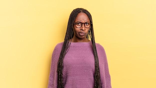 Afro-zwarte mooie vrouw die zich verward en twijfelachtig voelt, zich afvraagt of probeert te kiezen of een beslissing te nemen