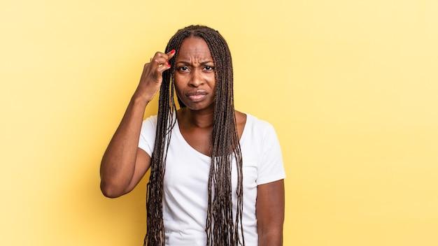 Afro-zwarte mooie vrouw die zich verward en verbaasd voelt en laat zien dat je gek, gek of gek bent