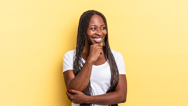 Afro zwarte mooie vrouw glimlachend met een gelukkige, zelfverzekerde uitdrukking met de hand op de kin, zich afvragend en opzij kijkend