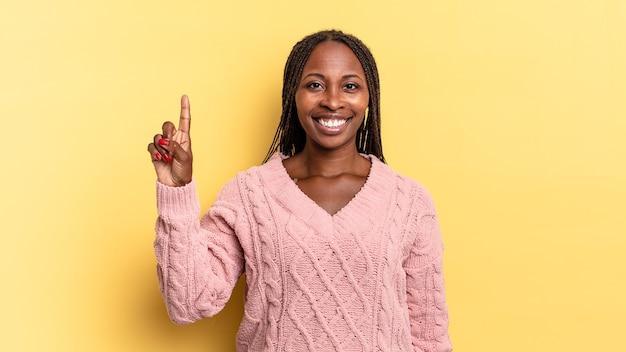 Afro-zwarte mooie vrouw glimlacht en ziet er vriendelijk uit, toont nummer één of eerste met hand naar voren, aftellend