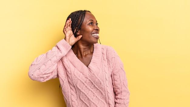 Afro-zwarte mooie vrouw lacht, kijkt nieuwsgierig opzij, probeert te luisteren naar roddels of een geheim af te luisteren