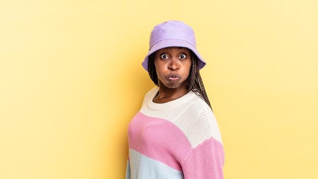 Afro zwarte mooie vrouw met een gekke, gekke, verbaasde uitdrukking, puffende wangen, vol, dik en vol eten