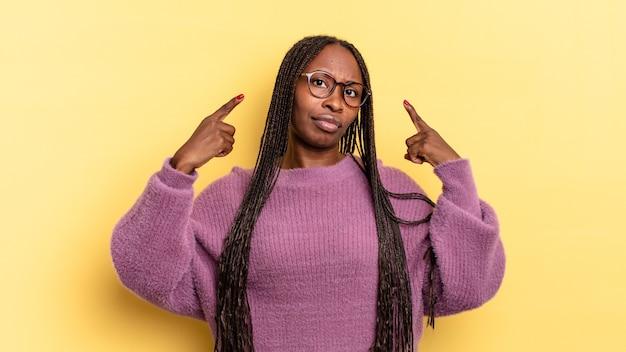 Afro-zwarte mooie vrouw met een slechte houding die er trots en agressief uitziet, naar boven wijst of een leuk teken maakt met handen