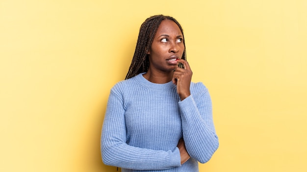 Afro-zwarte mooie vrouw met verbaasde, nerveuze, bezorgde of angstige blik, opzij kijkend naar kopieerruimte