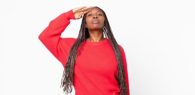 Afro zwarte volwassen vrouw die de camera begroet met een militaire groet in een daad van eer en patriottisme, respect tonen