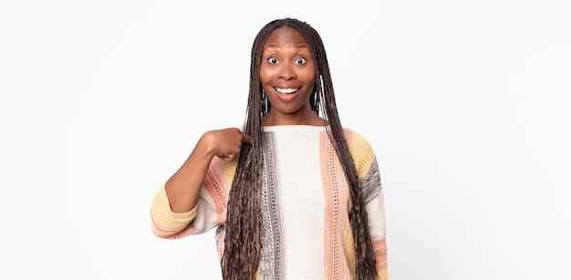 Afro zwarte volwassen vrouw die er blij, trots en verrast uitziet, vrolijk naar zichzelf wijst, zelfverzekerd en verheven is