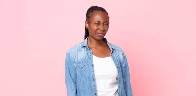 Afro-zwarte volwassen vrouw die er gelukkig en vriendelijk uitziet, lacht en je met een positieve houding aankijkt