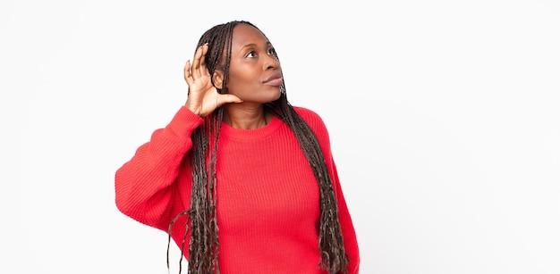 Afro-zwarte volwassen vrouw die er serieus en nieuwsgierig uitziet, luistert, probeert een geheim gesprek of roddel te horen, afluisteren