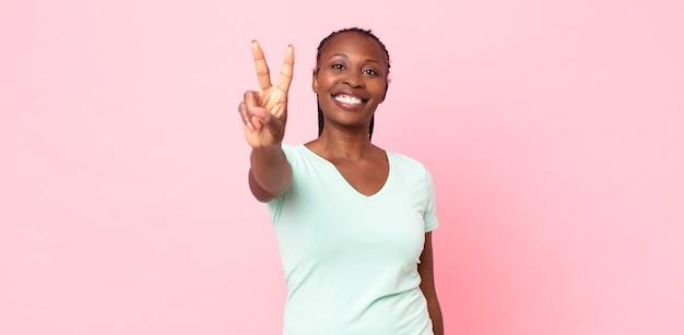Afro-zwarte volwassen vrouw die lacht en er gelukkig, zorgeloos en positief uitziet, gebarend overwinning of vrede met één hand