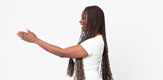 Afro zwarte volwassen vrouw die lacht, je groet en een handdruk aanbiedt om een succesvolle deal te sluiten, samenwerkingsconcept