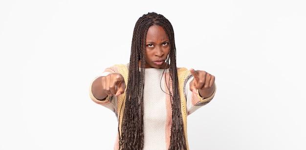 Afro-zwarte volwassen vrouw die met beide vingers en boze uitdrukking naar de camera wijst en je zegt dat je je plicht moet doen