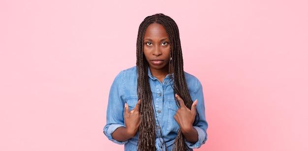 Afro zwarte volwassen vrouw die naar zichzelf wijst met een verwarde en vragende blik, geschokt en verrast om gekozen te worden