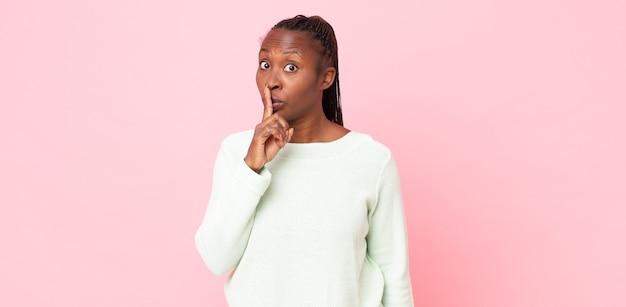 Afro-zwarte volwassen vrouw die om stilte en stilte vraagt, met de vinger voor de mond gebarend, shh zegt of een geheim houdt