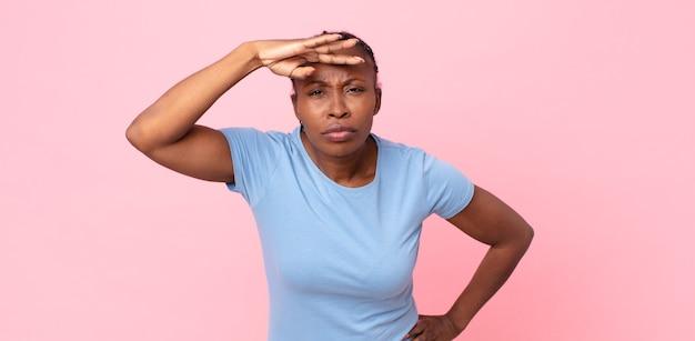 Afro zwarte volwassen vrouw die verbijsterd en verbaasd kijkt, met hand over voorhoofd ver weg kijkend, kijkend of zoekend