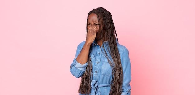Afro zwarte volwassen vrouw die walgt, haar neus vasthoudt om te voorkomen dat ze een vieze en onaangename stank ruikt