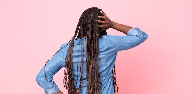 Afro-zwarte volwassen vrouw die zich geen idee en verward voelt, een oplossing denkt, met de hand op de heup en andere op het hoofd, achteraanzicht