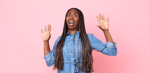 Afro zwarte volwassen vrouw die zich verdoofd en bang voelt, bang voor iets angstaanjagends, met de handen vooraan open en zegt blijf weg