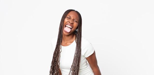 Afro zwarte volwassen vrouw met vrolijke, zorgeloze, rebelse houding, grappen maken en tong uitsteken, plezier maken